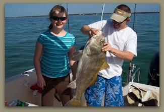 Capt Brad helps a young angler with her fish.